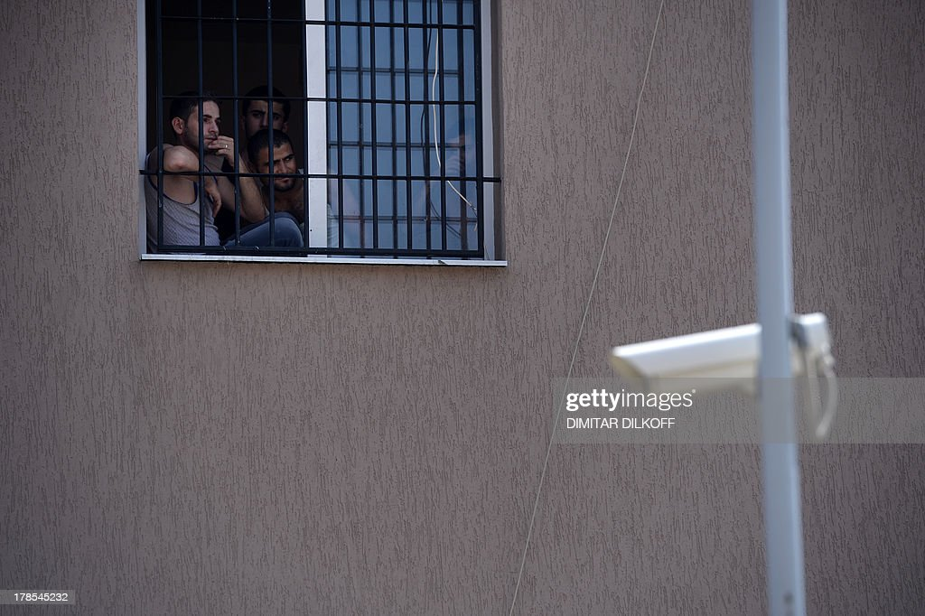 A picture taken on August 28, 2013, shows refugees behind barred windows at Bulgaria's shelter for clandestine migrants near Lyubimets, as the small EU state finds it hard to cope with an ever rising number of Syrians fleeing conflict at home. Over 3,100 clandestine migrants -- half of them Syrians -- have crossed into Bulgaria from neighbouring Turkey this year, doubling their numbers compared to 2012 and and causing Bulgaria's few temporary accommodation facilities to overflow. AFP PHOTO / DIMITAR DILKOFF STORY by Vessela SERGUEVA