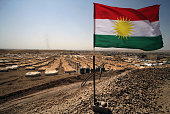 A picture taken on August 29 2013 shows the Kurdish flag waving in the wind above the Quru Gusik refugee camp 20 kilometres east of the of Arbil the...