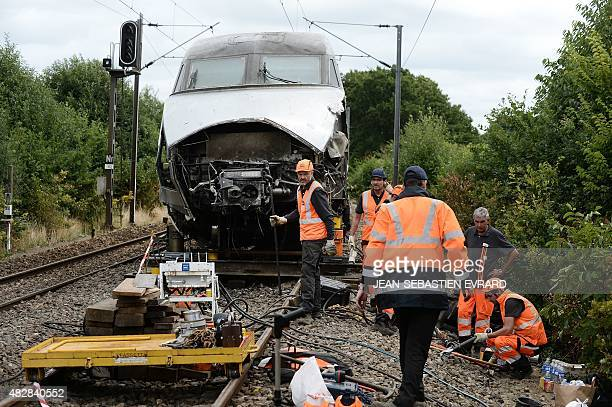 A picture taken on August 3 2015 in NoyalsurVilaine near Rennes western France shows employees of French national rail service SNCF walking next to a...
