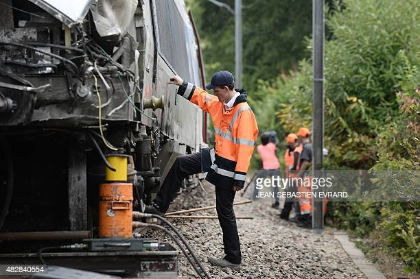 A picture taken on August 3 2015 in NoyalsurVilaine near Rennes western France shows employees of French national rail service SNCF standing next to...