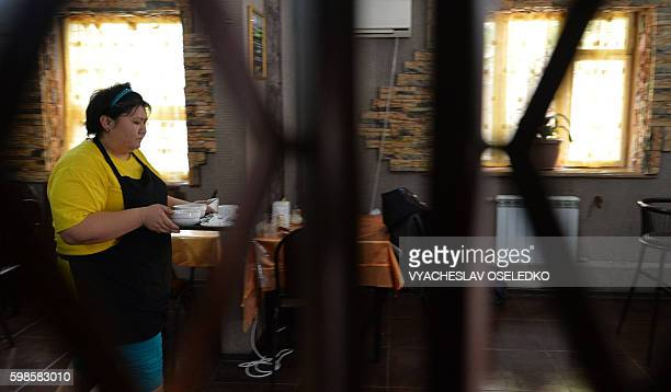 A picture taken on August 3 2016 shows a waitress carrying a tray with dirty dishes at the Training Cafe in Almaty With its simple menu and casual...