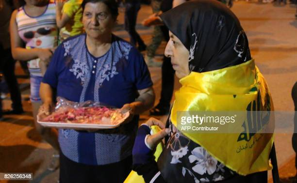 A picture taken on August 3 2017 shows a woman draped in the flag of the Lebanese Shiite Hezbollah movement awaiting the return of five of the...