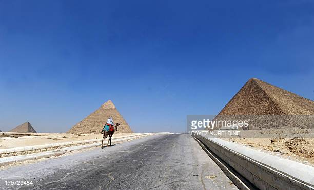 A picture taken on August 3 shows an Egyptian man riding his camel looking for customers in front of the pyramids of Khafre and Cheops in Giza...