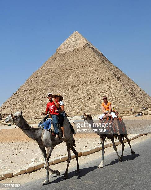 A picture taken on August 3 shows tourists and their guide riding camels past the pyramid of Khafre in Giza southwest of central Cairo By Giza's...