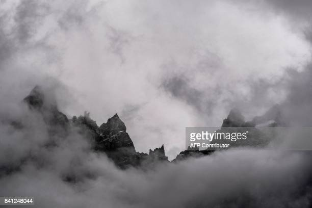 A picture taken on August 31 2017 in Chamonix shows the Aiguille du Midi peak in the fog ahead of the 15th edition of the Mount Blanc Ultra Trail...