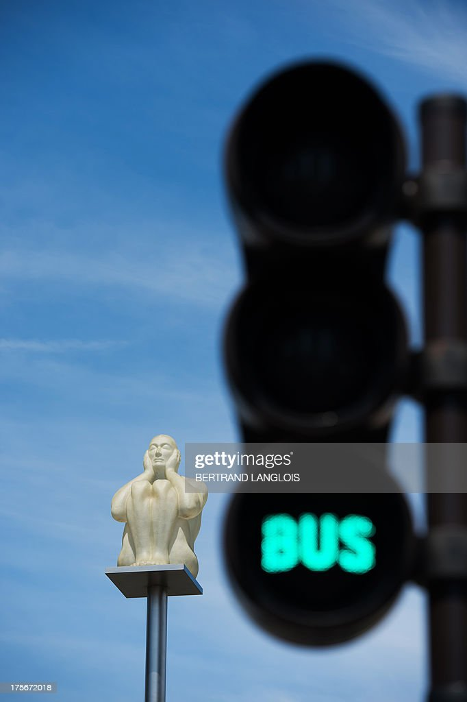 A picture taken on August 4, 2013 in Vitry-sur-Seine, outside Paris, shows the artwork 'Desir-Reve' (Desire-Dream) by Spanish artist Jaume Plensa viewed between traffic lights. Vitry-sur-Seine, a suburban residential town of concrete, has become in recent years one of the world's street art capitals, showcasing artists and must-see venues for this contemporary art movement which has turned its streets into an open-air gallery.