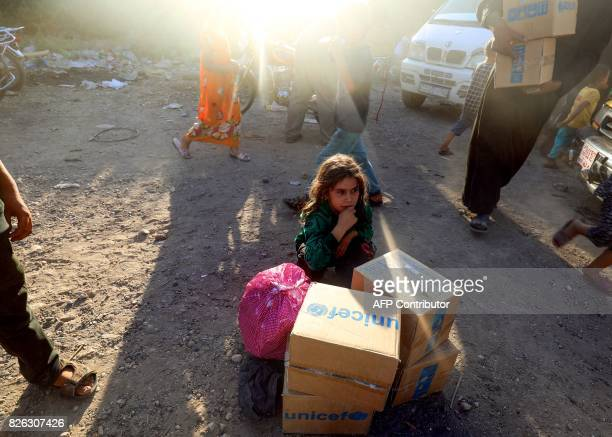 TOPSHOT A picture taken on August 4 2017 shows a displaced Syrian child who fled from the Islamic State group's Syrian stronghold of Raqa sitting...
