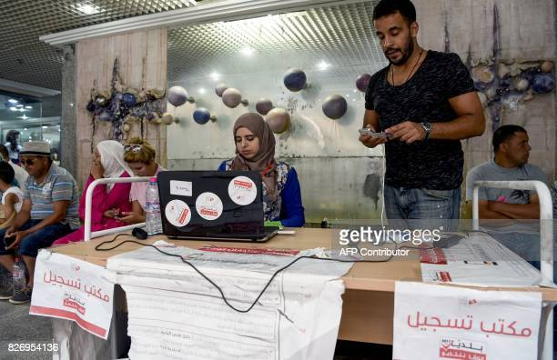 A picture taken on August 4 2017 shows employees of the Tunisian ISIE elections body sitting at an outreach booth at a shopping mall in the capital...