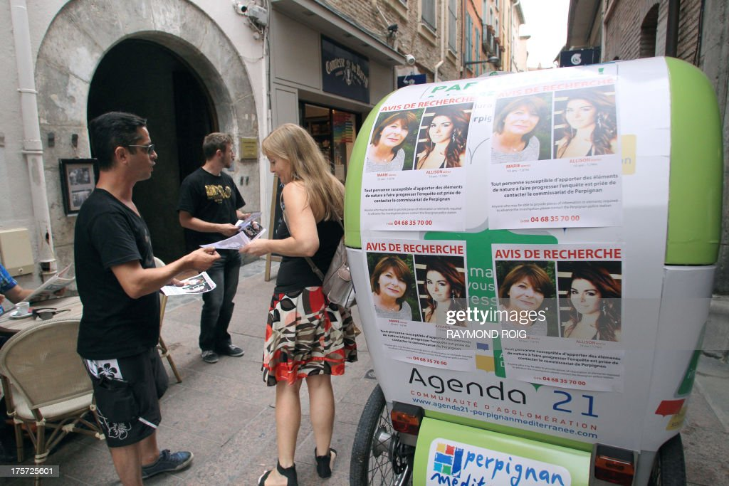 A picture taken on August 7, 2013 in Perpignan, southwestern France, shows friends of missing Allison Benitez distributing 'missing person' notices showing the portraits of Allison and her mother Marie-Josee. Police probing the disappearance of a beauty queen and her mother say they suspect foul play after it emerged her father's lover also went missing, in a new twist to a mystery that has gripped France. The disappearance of the father's Brazilian mistress in 2004 emerged as a key part of the investigation and 'made us lean towards a criminal theory,' a source close to the probe told AFP on August 9, 2013.