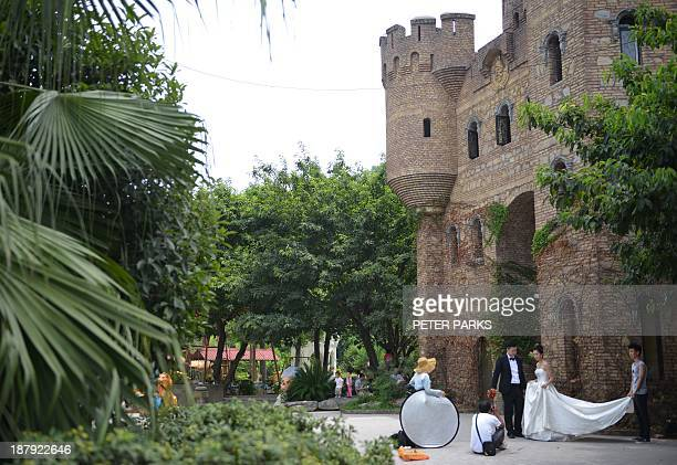 WITH 'CHINAECONOMYPROPERTYARCHITECTUREOFFBEATFEATURE' STORY Picture taken on August 8 2013 shows wedding photos being taken at one of the castles...