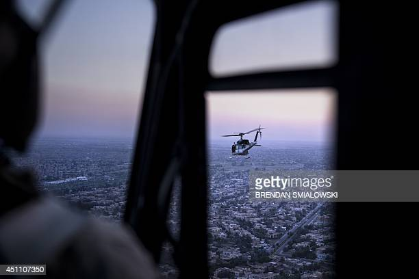 A picture taken on board a helicopter shows an US State Department helicopter flying over the Iraqi capital Baghdad as it transports US Secretary of...