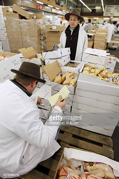 A picture taken on December 10 2010 shows salesmen working at the poultry and delicatessen products pavilion at Rungis international food market near...