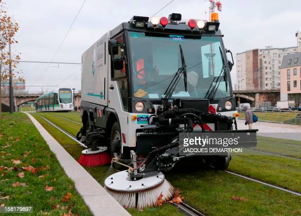 A picture taken on December 10 2012 shows a street cleaning vehicle at work as a T3b tramway operates on a test run at porte de La Villette in Paris...