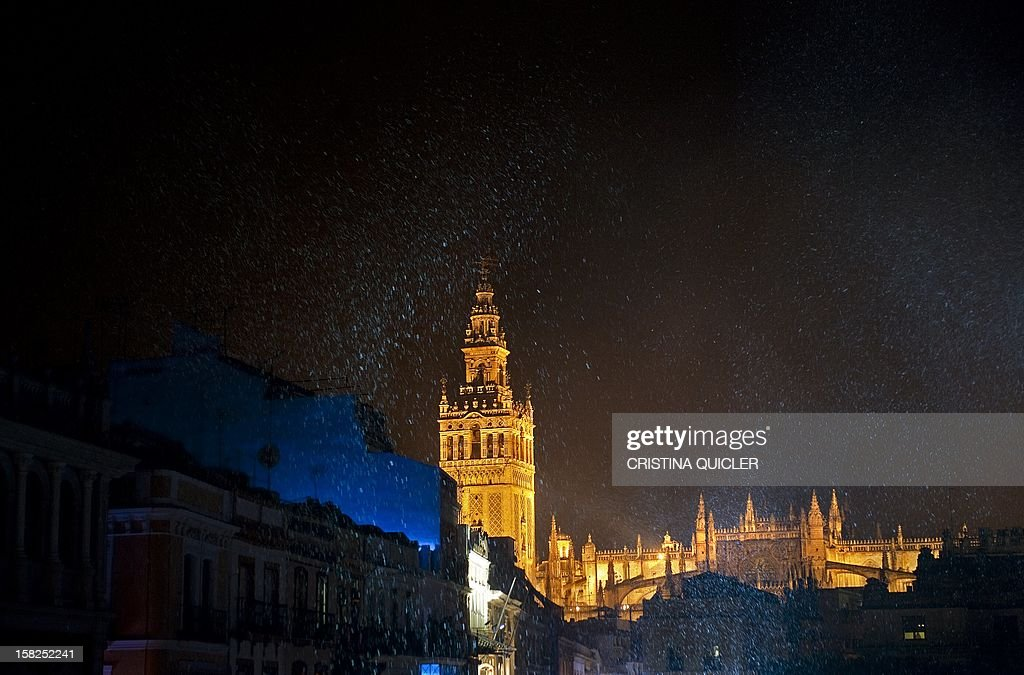 A picture taken on December 11, 2012 shows fake snowflakes falling in front of Sevilla's cathedral during a Christmas performance in Sevilla.