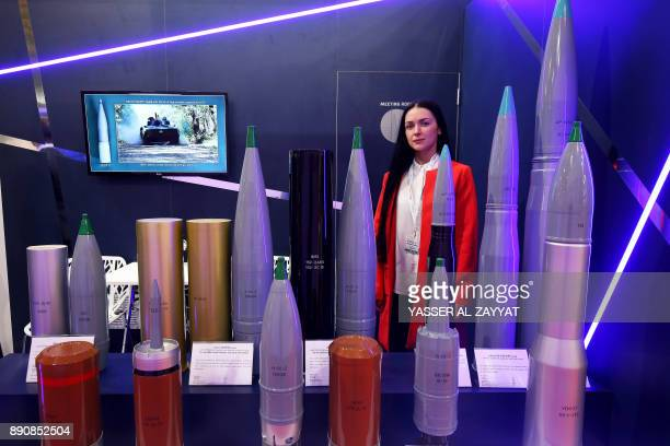 A picture taken on December 12 2017 shows Russian exhibitor standing next to heavy projectile rounds on display at the Gulf Defense and Aerospace...