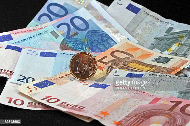 A picture taken on December 15 2011 in the northern city of Lille shows a coin of one Euro and banknotes of 5 20 and 50 Euros AFP PHOTO PHILIPPE...