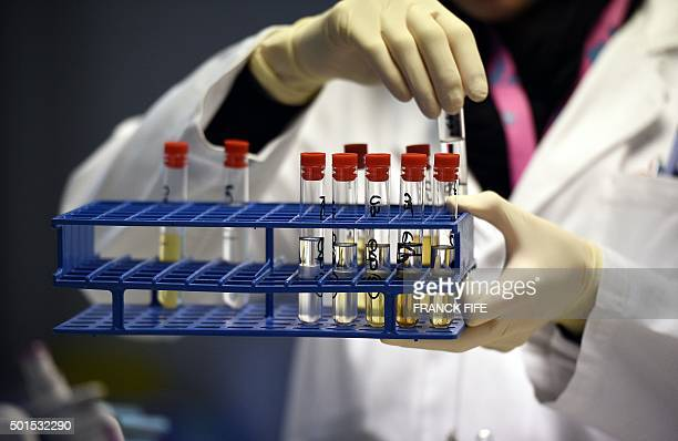 A picture taken on December 15 2015 shows a technician holding urine samples at the French national antidoping laboratory in ChatenayMalabry outside...