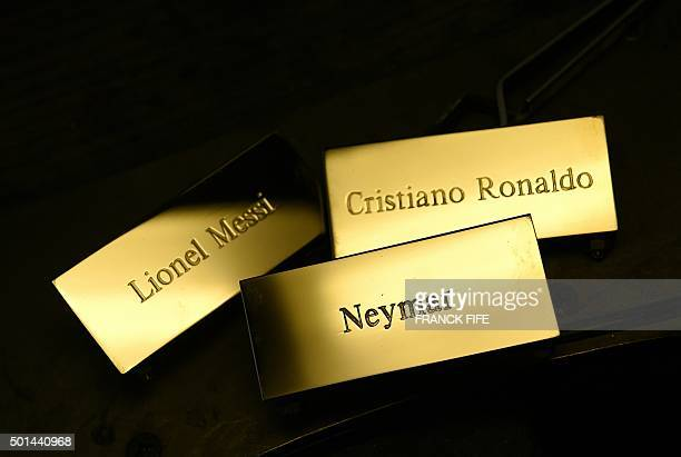 A picture taken on December 15 2015 shows three plaques reading 'Cristiano Ronaldo' 'Lionel Messi' and 'Neymar' at the Mellerio jewellers in Paris as...