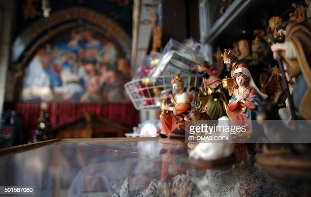 A picture taken on December 16 2015 in the West Bank city of Bethlehem shows a Christmas manger displayed in front of a Christian souvenir shop on...