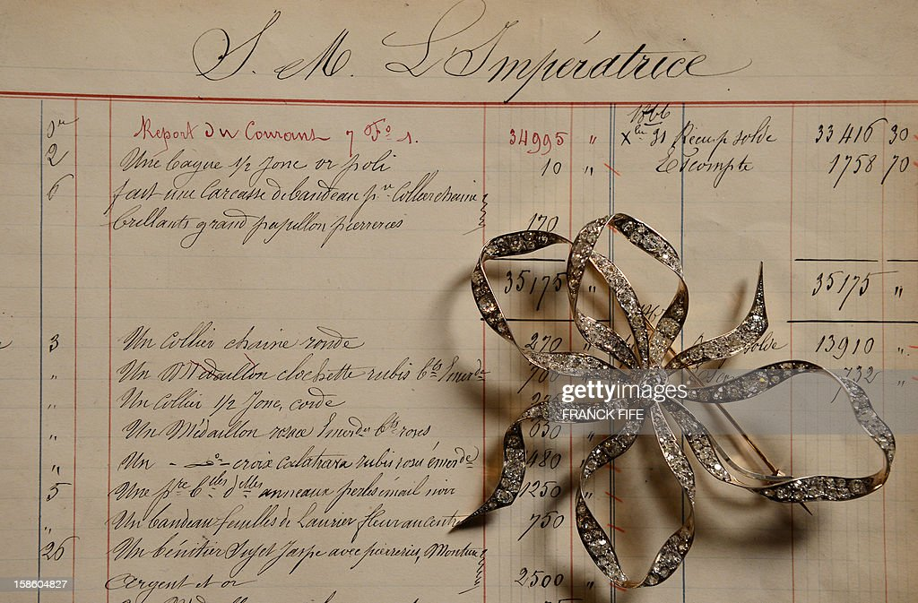 A picture taken on December 18, 2012 shows a 1860 silver gold large corsage pin node, displayed on a 1867 page order of Empress Eugenie, the wife of Napoleon III, Emperor of the French, in the Mellerio jewelry store in Paris. Founded in 1613, French jewelry house Mellerio is the oldest family-owned company in Europe and has been making the FIFA 'Ballon d'Or' trophy since 1956.