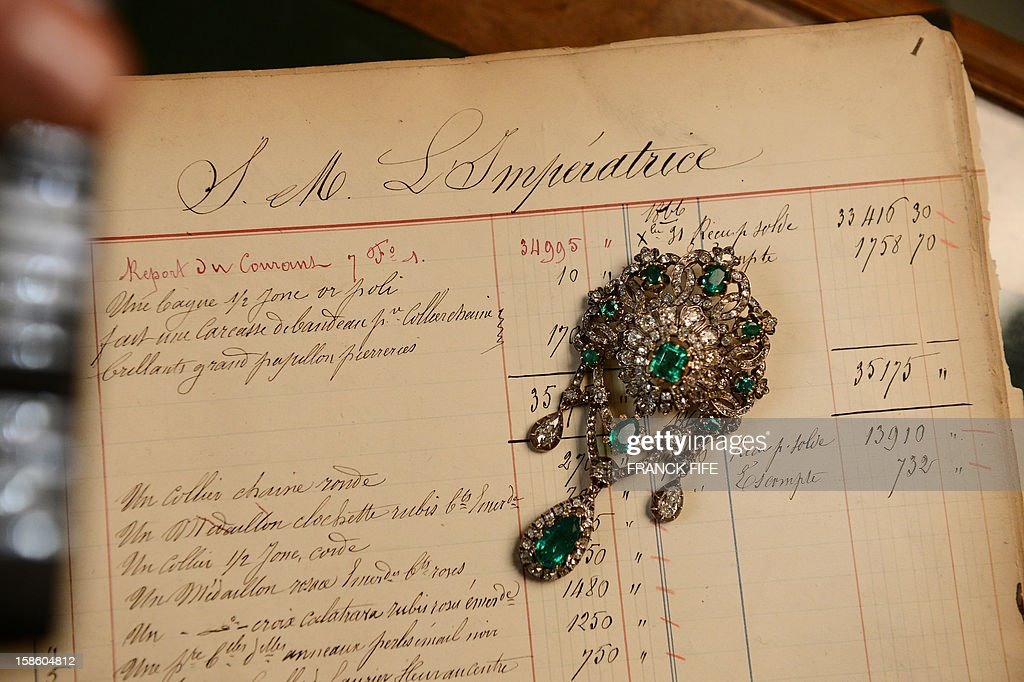 A picture taken on December 18, 2012 shows a corsage pin made of emeralds, diamonds, silver and gold, displayed on a 1867 page order of Empress Eugenie, the wife of Napoleon III, Emperor of the French, in the Mellerio jewelry store in Paris. Founded in 1613, French jewelry house Mellerio is the oldest family-owned company in Europe and has been making the FIFA 'Ballon d'Or' trophy since 1956. AFP PHOTO / FRANCK FIFE
