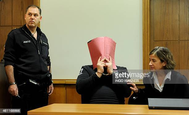 A picture taken on December 19 2014 shows former nurse Niels H charged with multiple murder and attempted murder of patients in handcuffs covering...