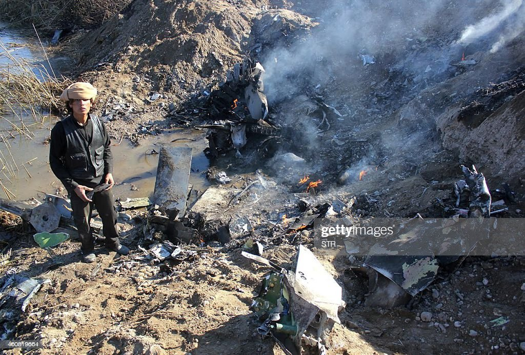 A picture taken on December 24 2014 reportedly shows an Islamic State group fighter collecting pieces from the remains of a Jordanian warplane from...