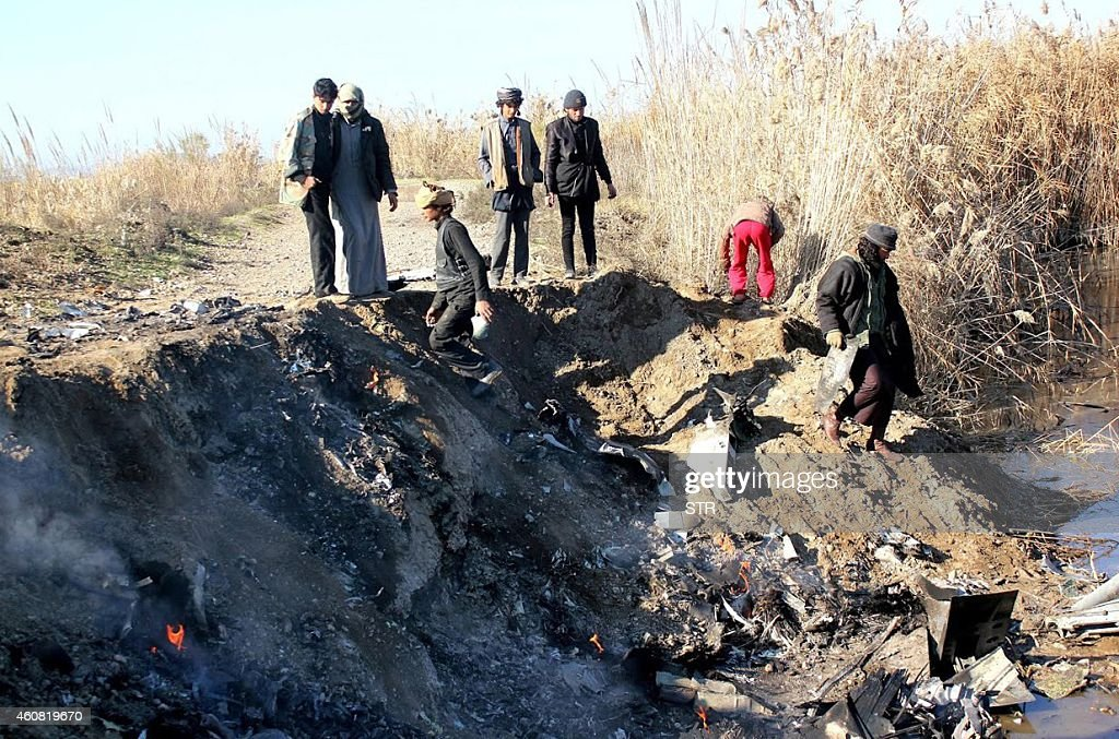A picture taken on December 24 2014 reportedly shows Islamic State group fighters collecting pieces from the remains of a Jordanian warplane from the...