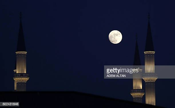 A picture taken on December 24 2015 shows the full moon over the minaret of a new mosque built inside the Turkish presidential palace in Ankara / AFP...
