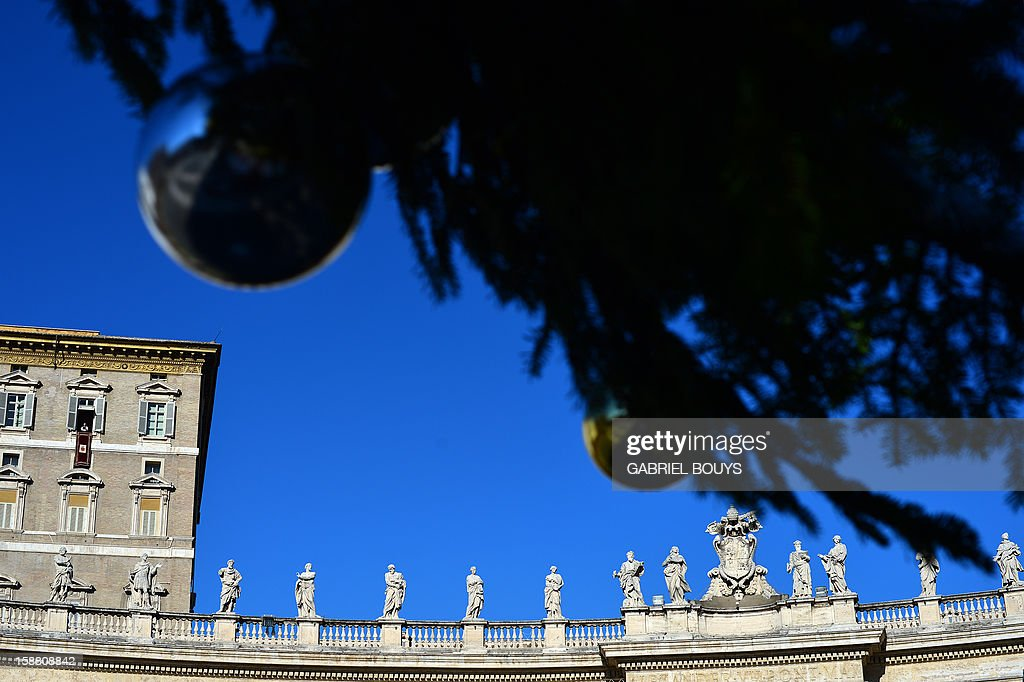 A picture taken on December 30, 2012 from underneath a Christmas tree shows Pope Benedict XVI (top floor, C) leading the Angelus prayer from a window of his apartments at the Vatican.