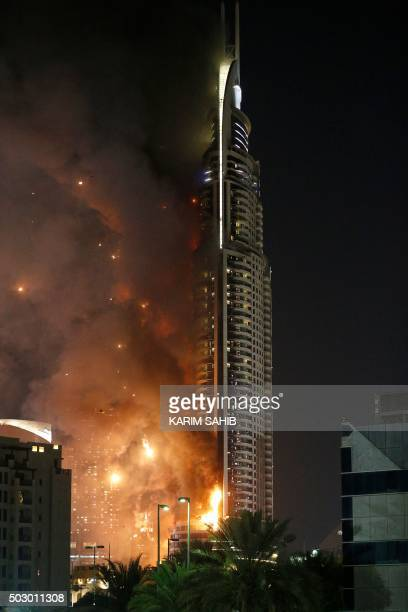 A picture taken on December 31 2015 shows the Address Downtown hotel burning after huge fire ripped through the luxury hotel near the world's tallest...