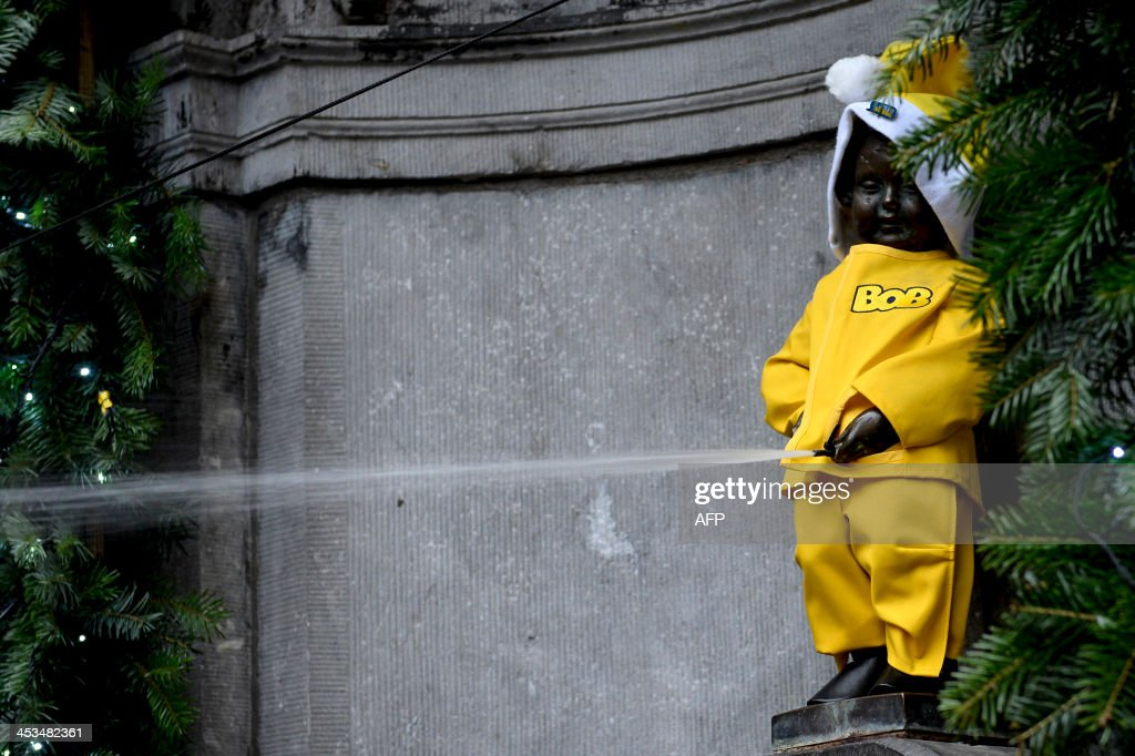 Picture taken on December 4, 2013 in Brussels, shows the Manneken Pis dressed as a yellow Santa Claus during the presentation of the 2013-2014 Bob-alcohol free drivers-campaign with 'Manneken Pis' and Santa Claus (Kerstman - Pere Noel) as figures of the campaign.