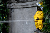 Picture taken on December 4 2013 in Brussels shows the Manneken Pis dressed as a yellow Santa Claus during the presentation of the 20132014...