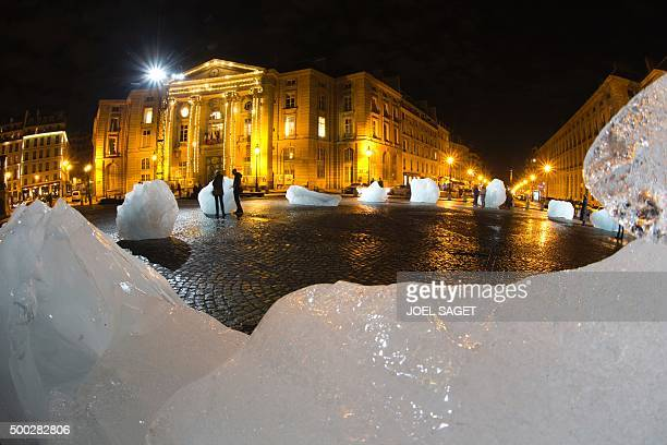A picture taken on December 6 2015 in Paris shows an art installation by a DanishIcelandic artist entitled 'Ice Watch' made with parts of Greenland's...