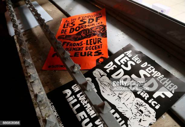 A picture taken on December 6 2017 shows leaflets and posters pasted by the Fondation Abbe Pierre foundation on a bank in Paris to highlight the use...
