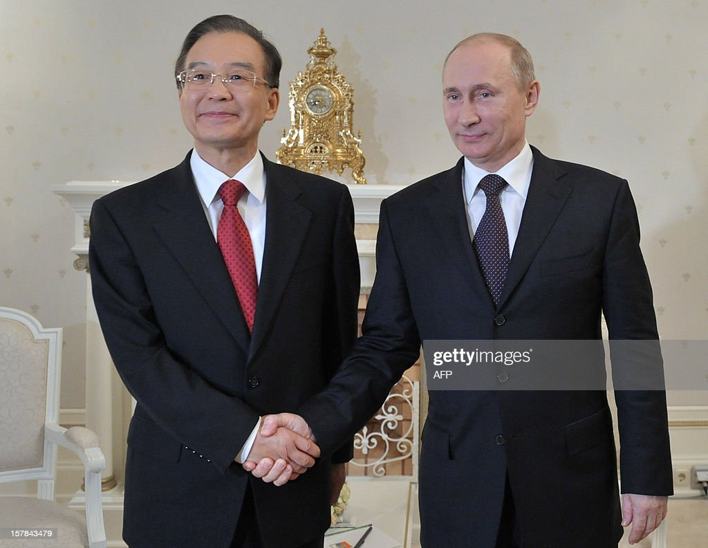 A picture taken on December 6, 2012, shows Russia's President Vladimir Putin (R) shaking hands with Chinese Prime Minister Wen Jiabao during their meeting in the Bocharov Ruchei residence in the Russian Black Sea resort of Sochi. Wen Jiabao is on a visit to Russia.