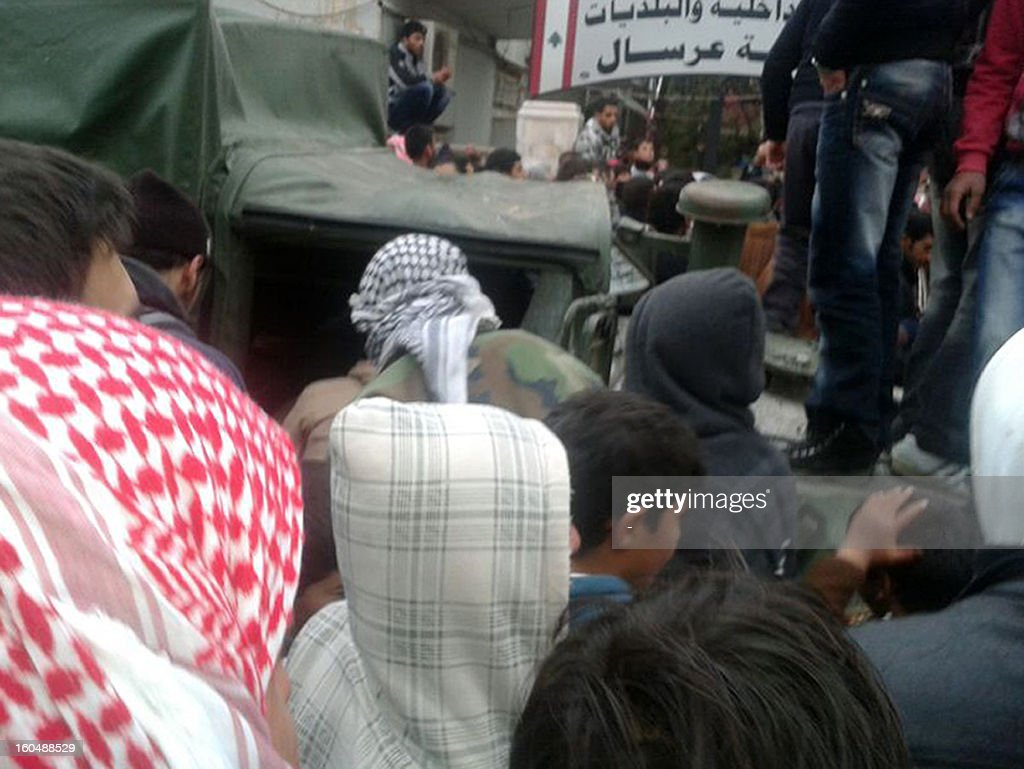 A picture taken on February 1, 2013 shows residents standing on the top of a military vehicle that was hit during a clash between gunmen and the army in which two soldiers were killed in Arsal, a village near the border with Syria. 'An army patrol was ambushed in Arsal as it hunted a man wanted for several terrorist acts,' the army said in a statement adding that 'an army captain and soldier were killed while several others were wounded in the clash'. Background is the municipality of Arsal. AFP PHOTO STR