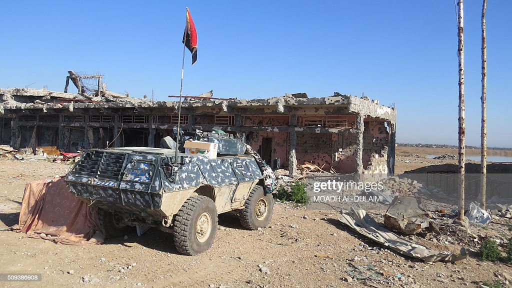A picture taken on February 10, 2016 shows an armoured vehicle of Iraqi pro-governement forces in front of a damaged building in the Saida area in the southern outskirts of Ramadi, after they retook the region from Islamic State (IS) group jihadists. / AFP / MOADH AL-DULAIMI
