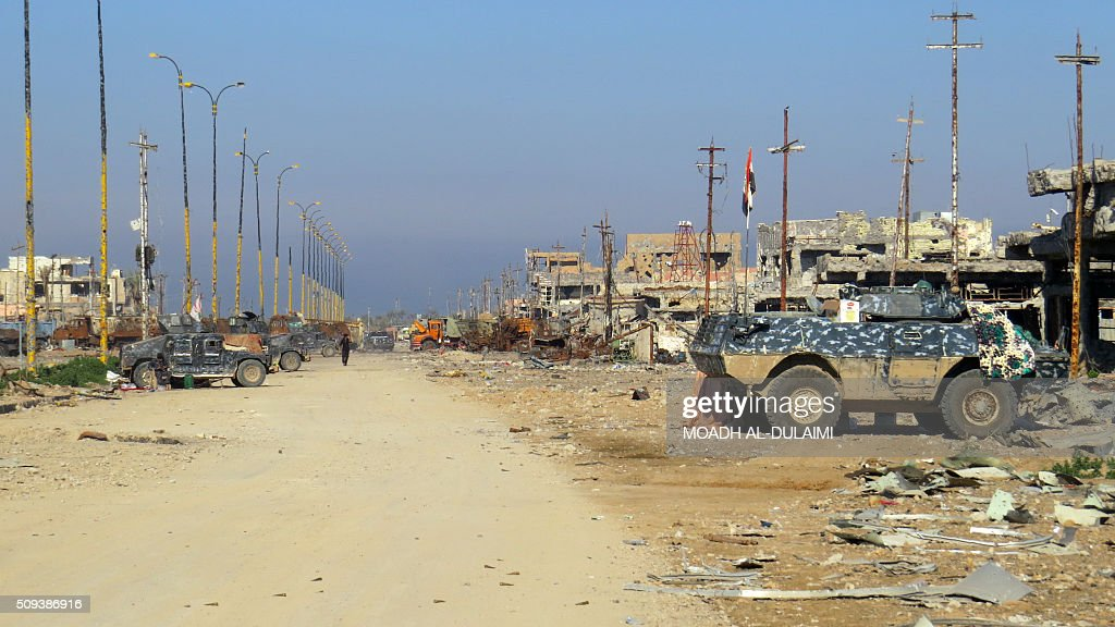 A picture taken on February 10, 2016 shows armoured vehicles of Iraqi pro-governement forces in front of damaged buildings in the Saida area in the southern outskirts of Ramadi, after they retook the region from Islamic State (IS) group jihadists. / AFP / MOADH AL-DULAIMI
