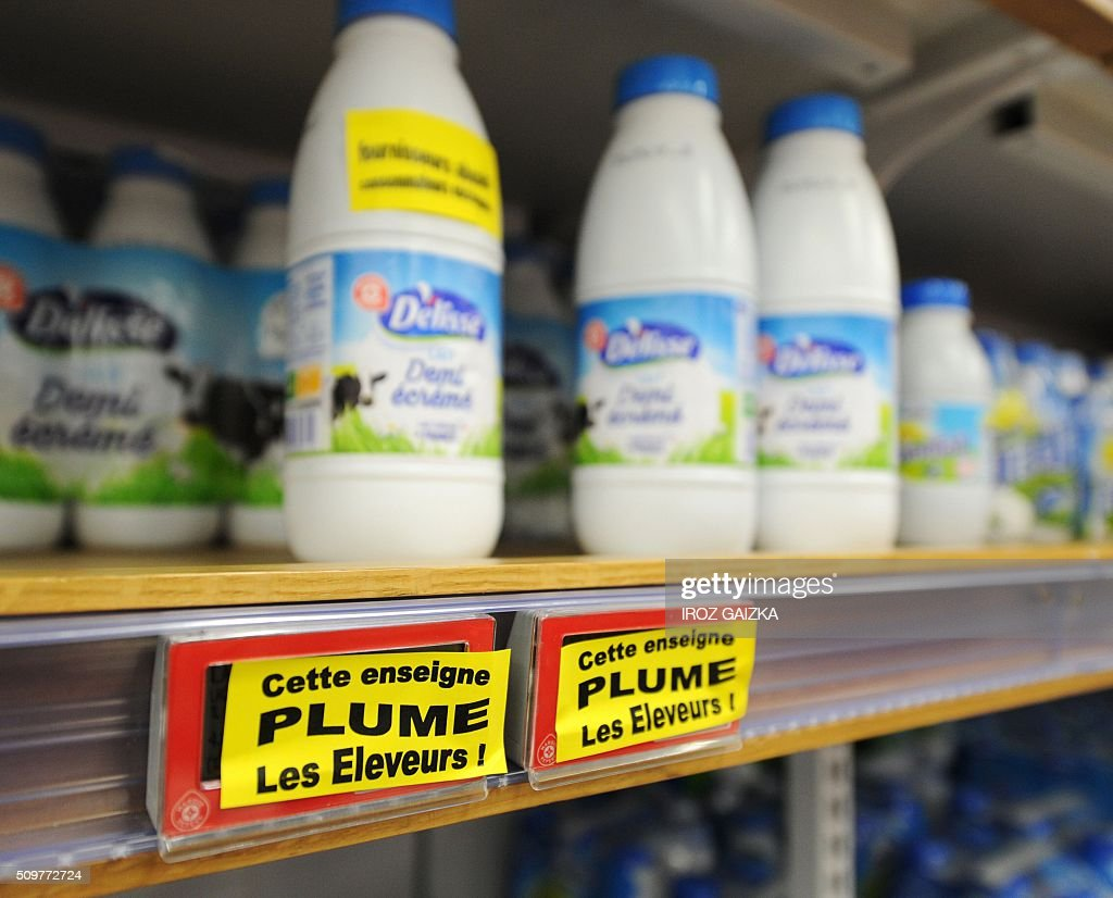 A picture taken on February 12, 2016 in Saint-Paul les Dax shows stickers reading 'This shop rips of farmers' stuck by young farmers in the milk shelves at Leclerc supermarket during a demonstration called by the trade-union 'Young Farmers' ('Jeunes Agriculteurs') to denounce the profits done by supermarkets. Nearly 15 young farmers gather and control prices and origins of the products sold in a Lecler supermarket in Saint-Paul les Dax on February 12, 2016. / AFP / IROZ GAIZKA