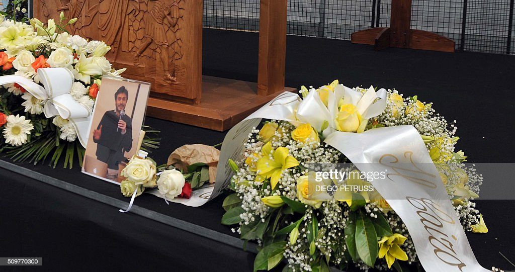 A picture taken on February 12, 2016 shows a picture of Giulio Regeni, a Cambridge University PhD student who was found dead bearing signs of torture after disappearing in Cairo last month, and tributes during his funeral in Fiumicello. / AFP / diego petrussi