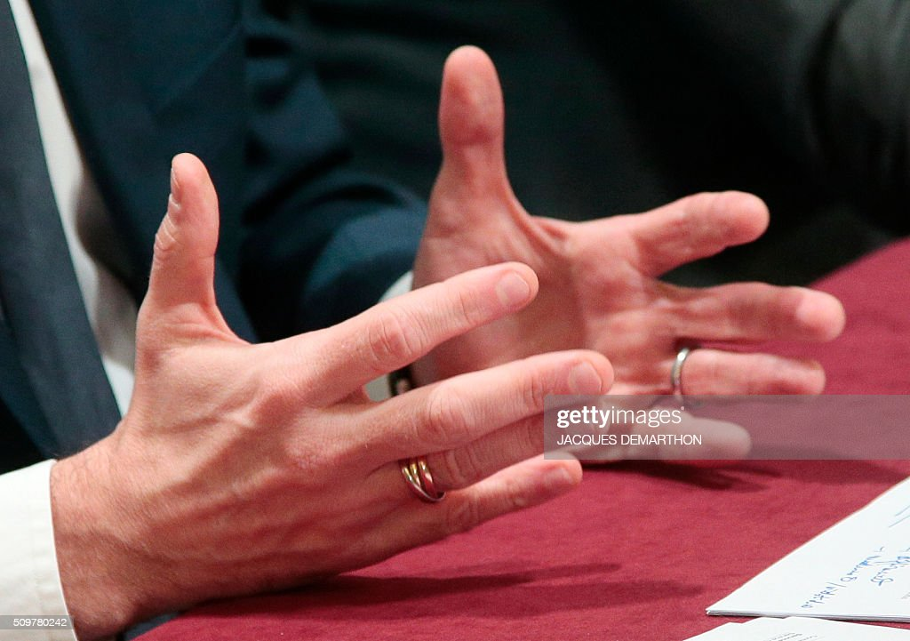 A picture taken on February 12, 2016 shows the hands of French Minister of Economy, Finance and Industry Emmanuel Macron during a press conference with France's Agriculture Minister after a meeting about trade relationships in agricultural and food-processing sectors, at the Agriculture Ministry in Paris. / AFP / JACQUES DEMARTHON