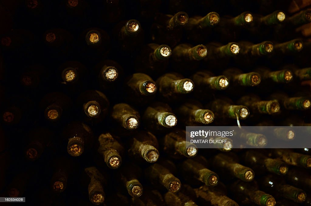 SERGUEVA -- A picture taken on February 14, 2013 shows dusty bottles of wine in Starata Izba (The old cellar) in the village of Parvenetz. Starata Izba, in the south of Bulgaria, founded in the 19th century but neglected after the fall of communism in 1989, has come back to life thanks to a Bulgarian-French team who have introduced to it their knowledge of Bordeaux winemaking.