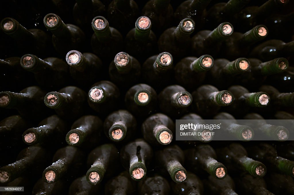 SERGUEVA -- A picture taken on February 14, 2013 shows dusty bottles of wine in Starata Izba (The old cellar) in the village of Parvenetz. Starata Izba, in the south of Bulgaria, founded in the 19th century but neglected after the fall of communism in 1989, has come back to life thanks to a Bulgarian-French team who have introduced to it their knowledge of Bordeaux winemaking. AFP PHOTO / DIMITAR DILKOFF