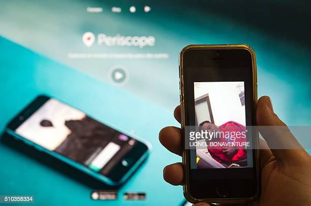 A picture taken on February 15 2016 in Paris shows a person watching on a smartphone a replay of a live video recorded on February 13 2016 by Paris...