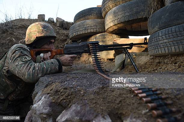 A picture taken on February 16 2015 shows an Armenian serviceman guarding an area near the village of Movses close to the border with Azerbaijan The...