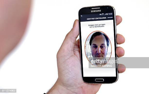 A picture taken on February 19 2016 shows a man using a smartphone with an app that allows online payments using biometric authentication in...