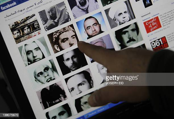 A picture taken on February 2 2012 in the Lebanese capital Beirut shows a man pointing to pictures of people allegedly killed during the 1982 Hama...