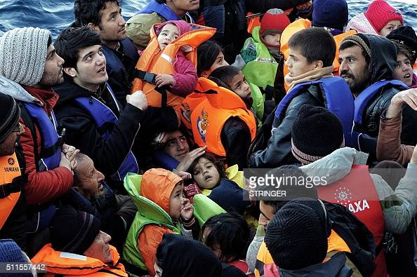 A picture taken on February 20 2016 shows children among refugees and migrants on a rubber boat on their way from Turkey to the Greek northern island...