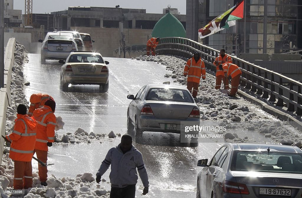 A picture taken on February 21 2015 shows Jordanian city cleaners in their orange jumpsuit uniforms working on cleaning snow from the streets of the...